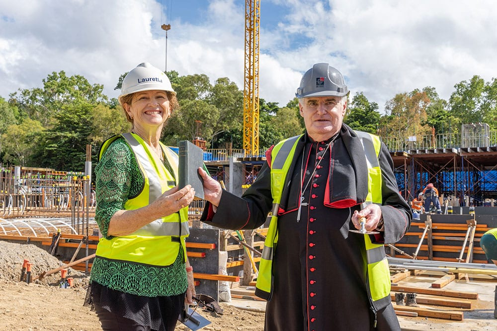 Newman Catholic College Foundation Principal Dr Lauretta Graham and Cairns Bishop James Foley with a trowel from the Dioscean Archives previously used at St Michael's School, Gordonvale and St Monica's College, Cairns. Bishop James gave Dr Graham a book about Cardinal John Henry Newman's works, which came from the Bishop's personal collection and was published in 1902.